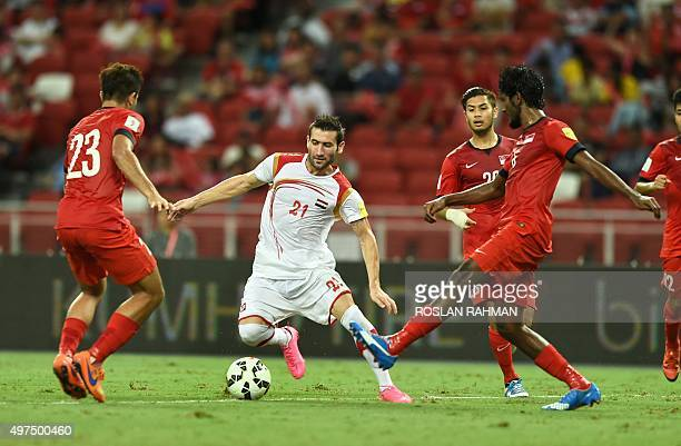 Syria's Fahad Youssef vies for the ball with Singapore players during their 2018 FIFA Group E World Cup qualifier football match in Singapore on...