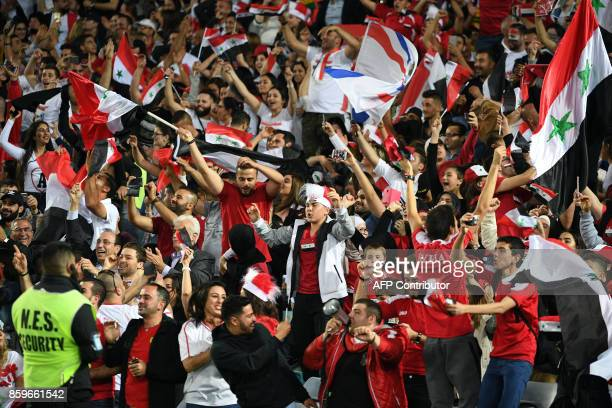 Syria's fan celebrate their first goal against Australia during their 2018 World Cup football qualifying match in Sydney on October 10 2017 / AFP...