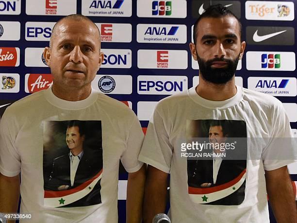 Syria's head coach Fajr Ibrahim and footballer Osama Omari pose with a teeshirt bearing the portrait of Syrian President Bashar alAssad after their...