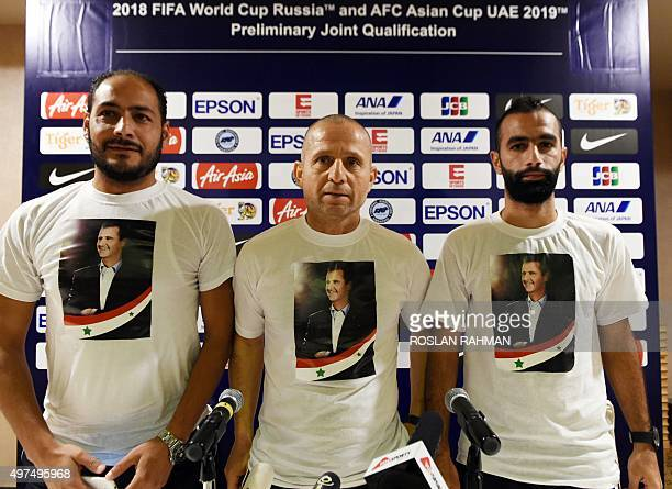 Syria's head coach Fajr Ibrahim and his player Osama Omari wear tshirts with a portrait of their President Bashar alAssad as they pose for...