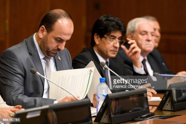 Syria's main opposition High Negotiations Committee leader Nasr alHariri reads documents during a meeting with UN Special Envoy for Syria during...