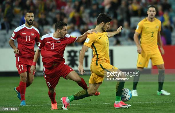Syria's Mouaiad Ajjan fights for ball with Australia's Mathew Leckie during their 2018 World Cup football qualifying match in Sydney on October 10...