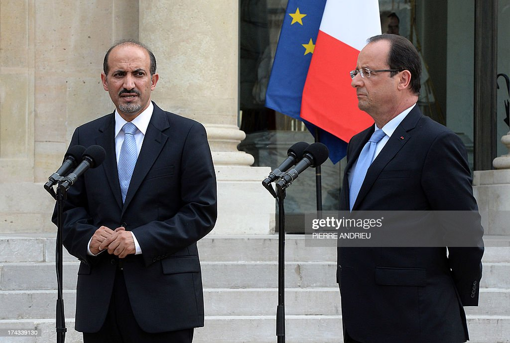 Syria's new opposition leader Ahmad Jarba (L) speaks to the media after a meeting with France President François Hollande (R) at the Elysee presiential palace on July 24, 2013 in Paris. Jarba asked France the day before for military aid to boost the forces fighting the regime of President Bashar al-Assad.