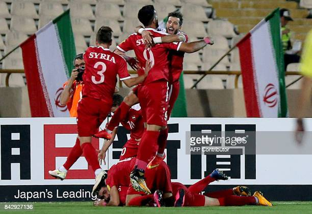 Syria's players celebrate after scoring a goal against Iran during the FIFA World Cup 2018 qualification football match between Iran and Syria at the...