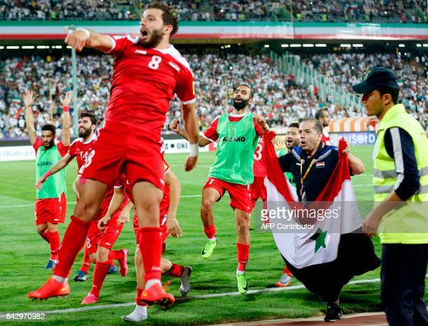 Syria's players celebrate at the end of their FIFA World Cup 2018 qualification football match against Iran at the Azadi Stadium in Tehran on...