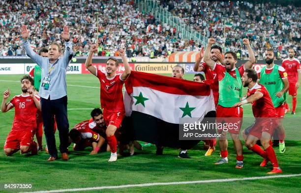 TOPSHOT Syria's players celebrate at the end of their FIFA World Cup 2018 qualification football match against Iran at the Azadi Stadium in Tehran on...