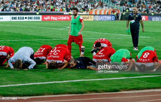 Syria's players pray at the end of their FIFA World Cup 2018 qualification football match against Iran at the Azadi Stadium in Tehran on September 5...