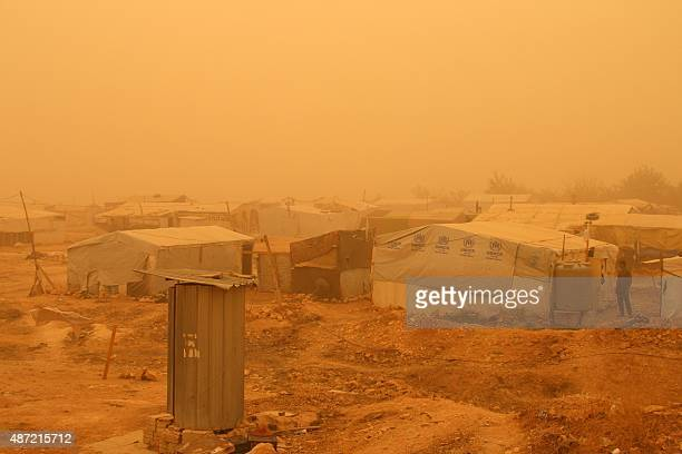 Syriasn talk in front of a tent during a sandstorm on September 7 2015 at a refugee camp on the outskirts of the eastern Lebanese city of Baalbek AFP...