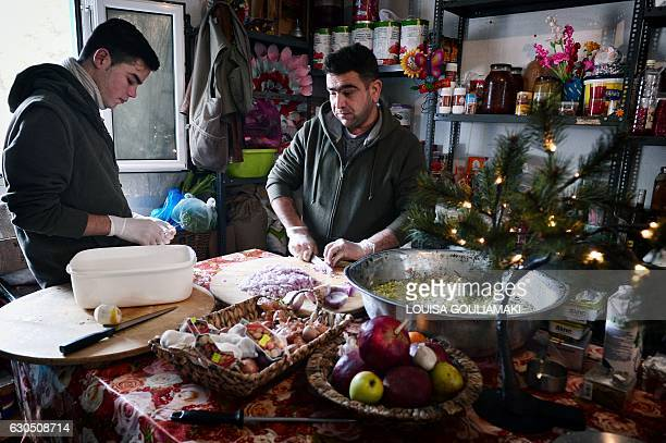 Syrina volunteers help to prepare a meal in the kitchen of 'cafe Rits' in Ritsona refugee camp some 80 km north of Athens on December 21 2016 Before...