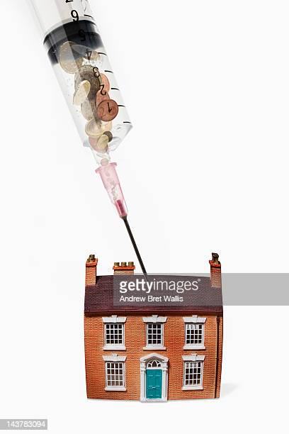 Syringe filled with coins injecting a model house