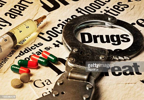 Syringe, pills and handcuffs on stained drug-related headlines