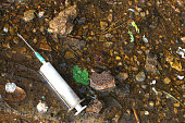 A syringe thrown away in the forest. Used drug addict's syringe on the ground.