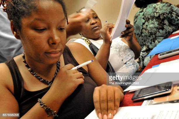 SyroneWoodard reviewed her paperwork for her son a fourth grader at the DC Opportunity Scholarship Program application workshop on June 25 2011 in...