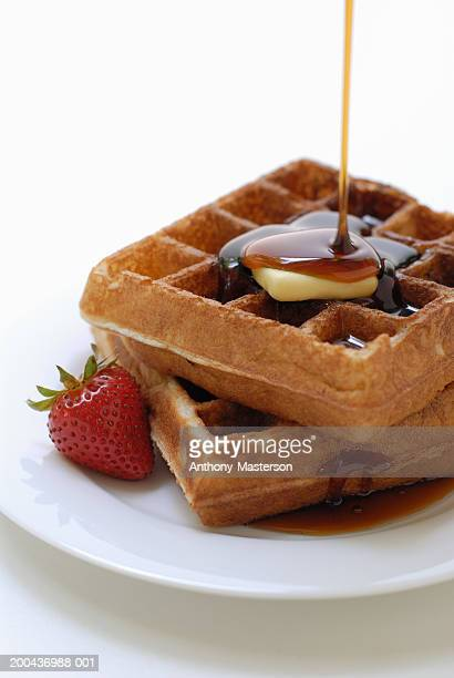 Syrup being poured over waffles