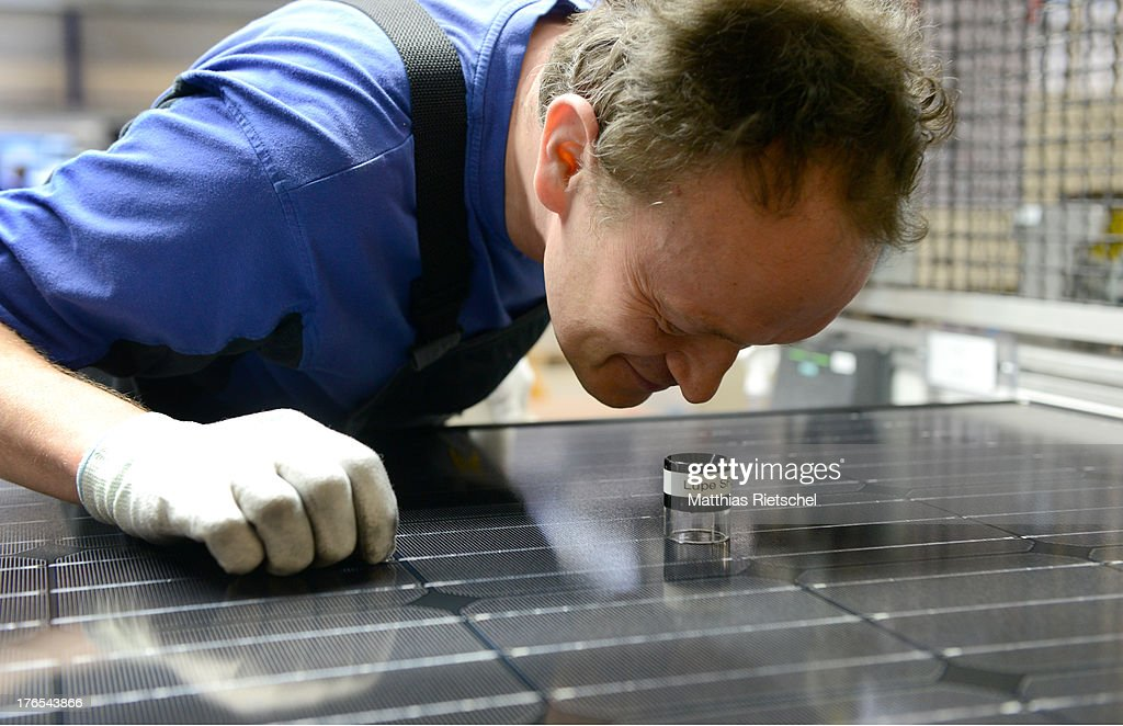 System administrator Holm Goehler checks with a magnifying glass the surface of a finished solar energy modul in the assembly line at the Solarworld plant on August 14, 2013 in Freiberg, Germany. The troubled solar cells, modules and panels producer managed to recently avoid bankruptcy by reaching an agreement with its shareholders and other investors. Many solar energy equipment producers in Germany are facing difficult times due to stiff competition from China.