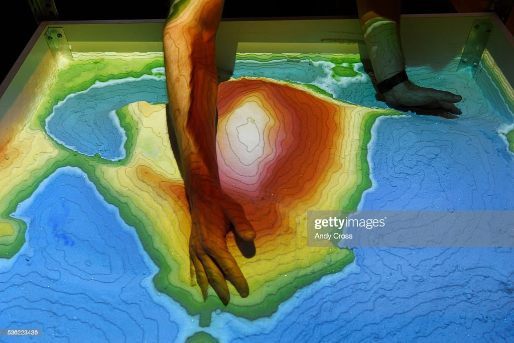 System76 CEO and founder Carl Richell makes a colorful topographical mountain of sand in the Augmented Reality Sandbox that System76 designed at the offices May 31, 2016. The computerized typography and color changes with every movement in the sandbox.