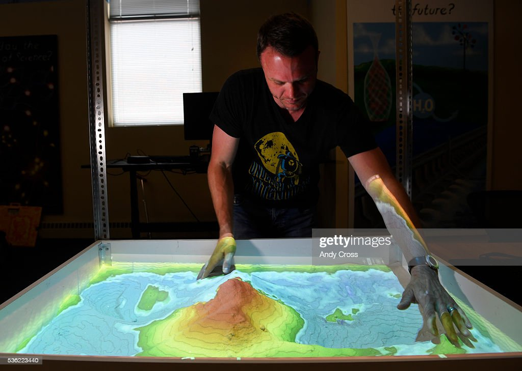 System76 CEO and founder Carl Richell makes a colorful topographical mountain of sand in the Augmented Reality Sandbox that System76 designed at the offices May 31, 2016. The typography and color changes with every movement in the sandbox.