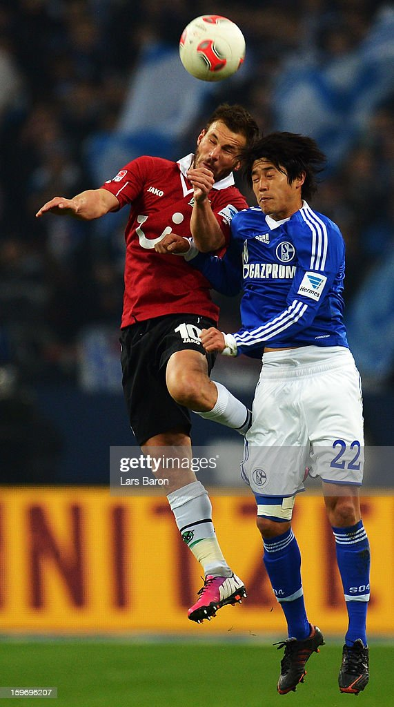 Szabolcs Huszti of Hannover goes up for a header with Atsuto Uchida of Schalke during the Bundesliga match between FC Schalke 04 and Hannover 96 at Veltins-Arena on January 18, 2013 in Gelsenkirchen, Germany.
