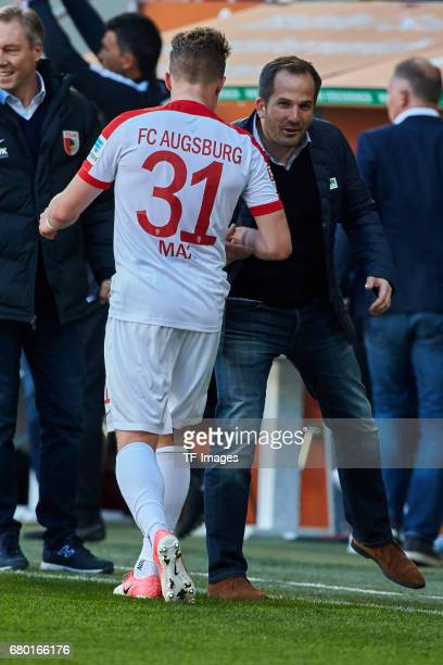 t Philipp Max of Augsburg shakes hands with Head coach Manuel Baum of Augsburg during the Bundesliga match between FC Augsburg and Hamburger SV at...