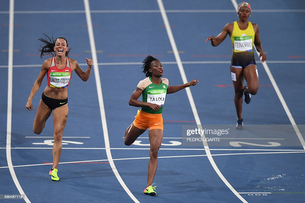 ta Ivory Coast's MarieJosee Ta Lou crosses the finish line ahead of Bulgaria's Ivet LalovaCollio as they compete in the Women's 200m Semifinal during...