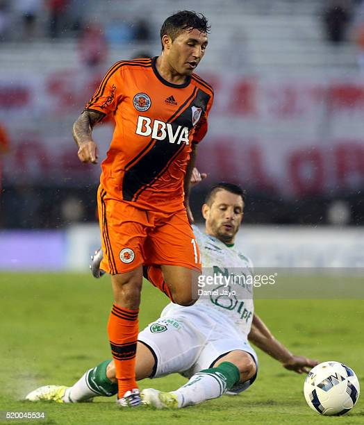 Tabare Viudez of River Plate is tackled by Guillermo Cosaro of Sarmiento during a match between River Plate and Sarmiento as part of Torneo...