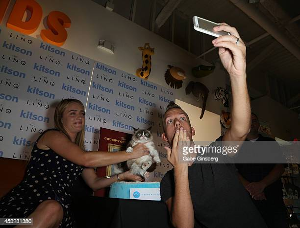 Tabatha Bundesen holds Grumpy Cat as blogger JSon Dinant takes a photo at 'The Grumpy Guide to Life Observations By Grumpy Cat' book launch at Kitson...