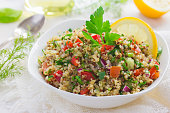 Tabbouleh salad with quinoa, parsley and vegetables on white background