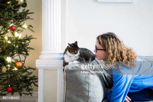 tabby cat and a young girls looking at each other on a sofa beside a christmas tree