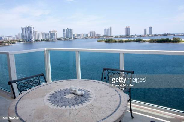 Table and chairs on balcony overlooking city skyline, Miami, Florida, United States