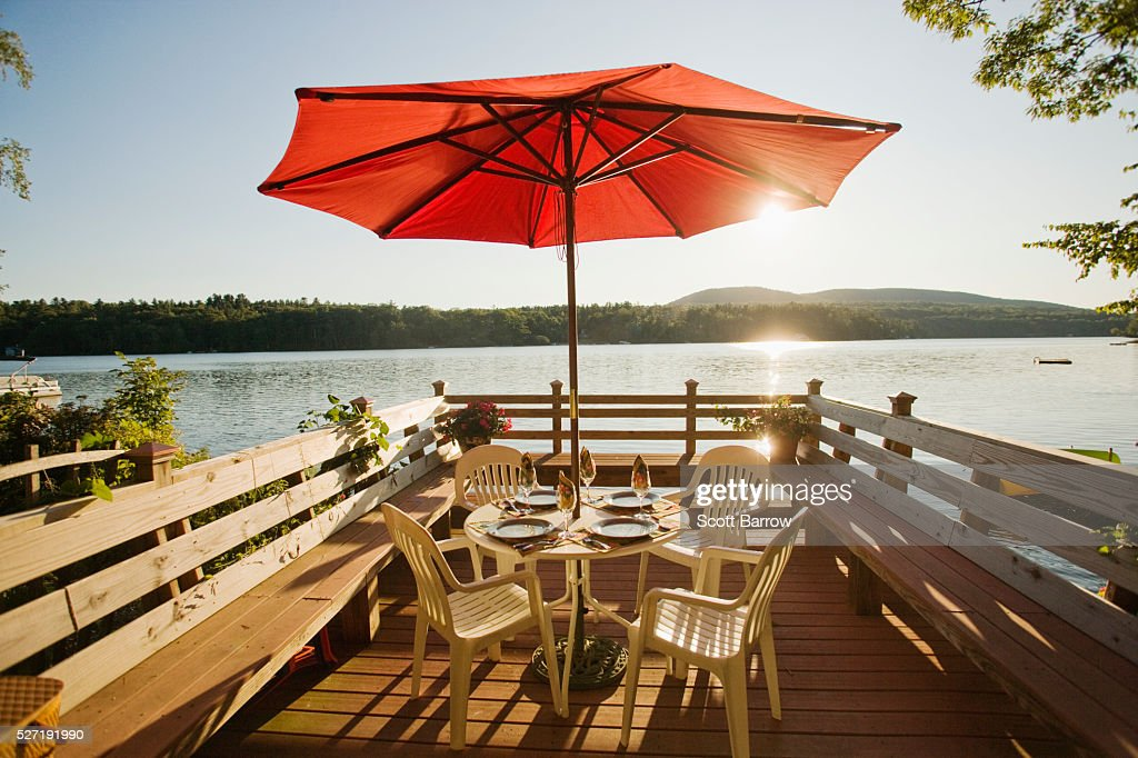 Table and chairs with umbrella on a deck beside a lake : Photo