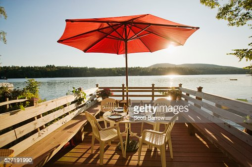 Table and chairs with umbrella on a deck beside a lake : Stock Photo