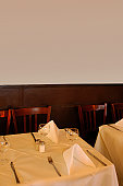 Table at restaurant, tablecloth, cutlery, wine glasses, napkins, wooden panelling