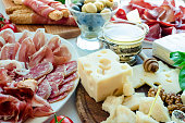 Table full of mediterranean appetizers, tapas or antipasto. Assorted Italian food set. Delicious snack on party or picnic time. Chopping board with meat and cheese. Italian style banquet.