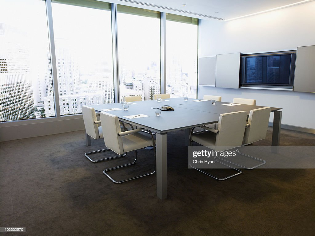 Table in conference room overlooking city : Stock Photo