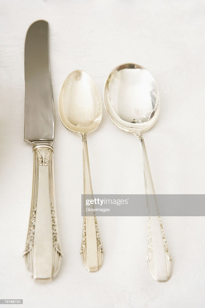 Table knife with two spoons on a dining table : Stock Photo