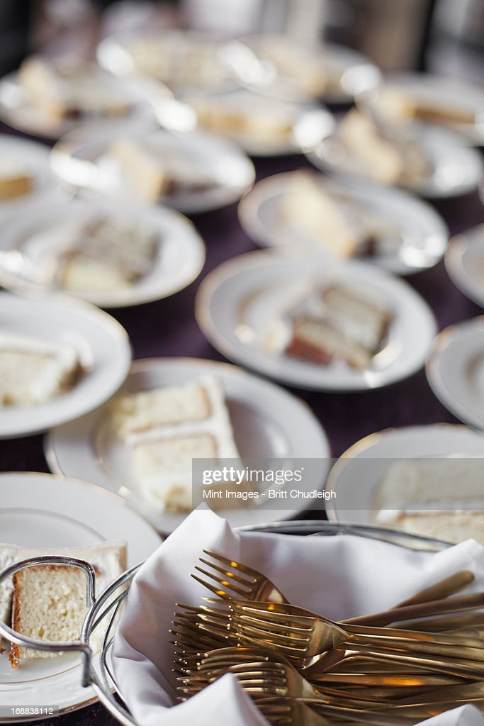A table laden with plates. White china, and a basket full of dessert forks. A slice of wedding cake.  : Stock Photo