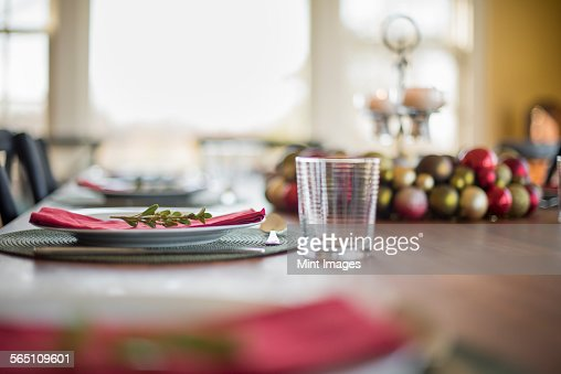 A table laid for a celebration meal. Christmas ornaments, decorations and a candle in a candle holder.