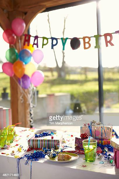 Table laid for birthday party with balloons and streamers