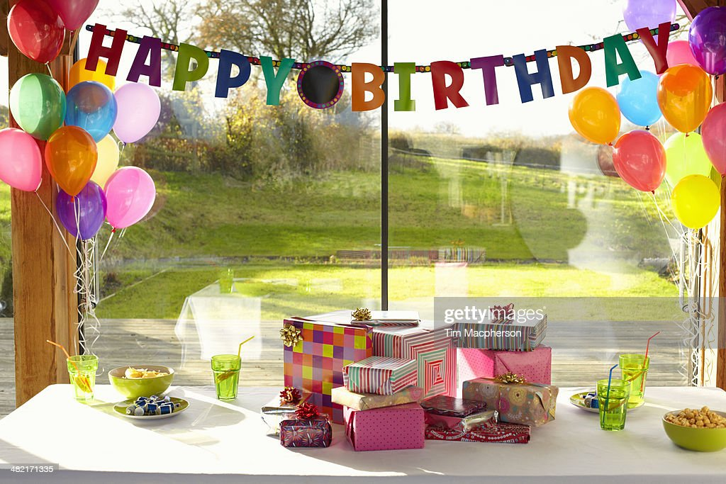 Table laid with birthday gifts and balloons