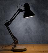 Table lamp on wooden desk on black background