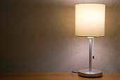 Table lamp over white wall background. Modern minimalistic night light, decorative element for bedroom interior.