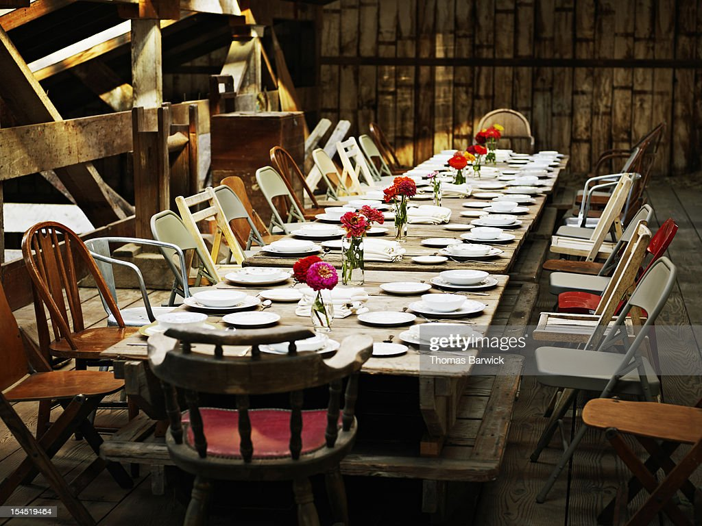 Table set for dinner inside rustic building : Stock Photo