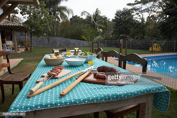 Table set for dinner on lawn besid epool