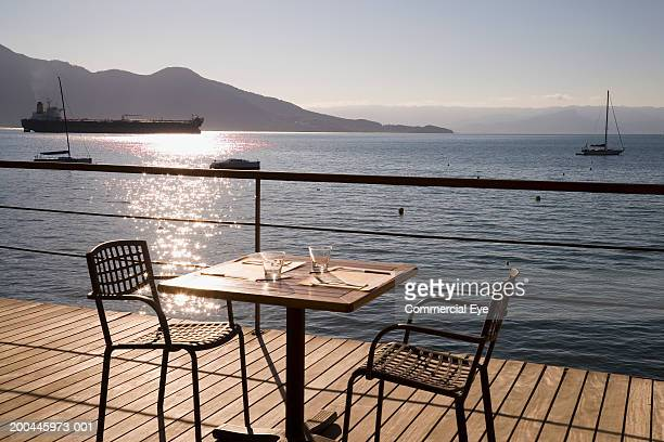 Table set for two on deck overlooking bay, sunset