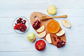 Honey, apple slices and pomegranate serve on kitchen board top view. Table set with traditional food for Jewish New Year Holiday, Rosh Hashana.