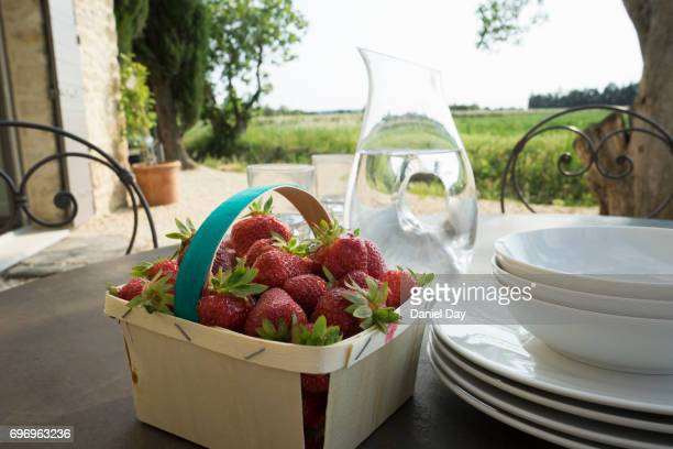 Table setting on a farm in France with late afternoon light and fresh strawberries