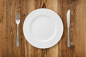 Table setting on rustic wood background - plate, fork and knife