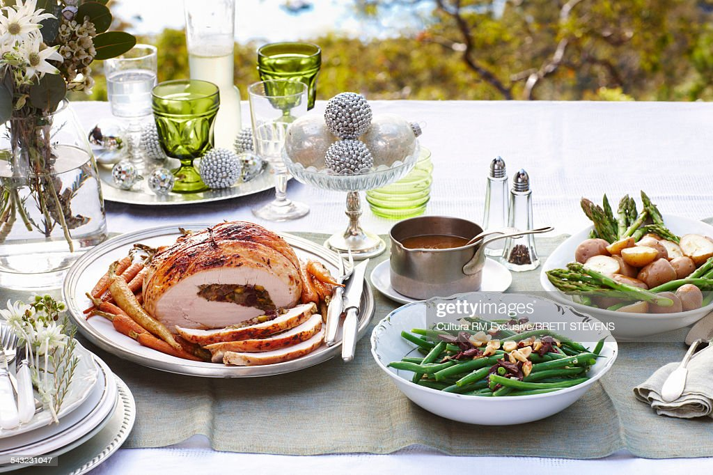 Table setting outdoors with Christmas turkey and vegetables