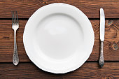 Empty Plate with Knife and Fork on Kitchen Table