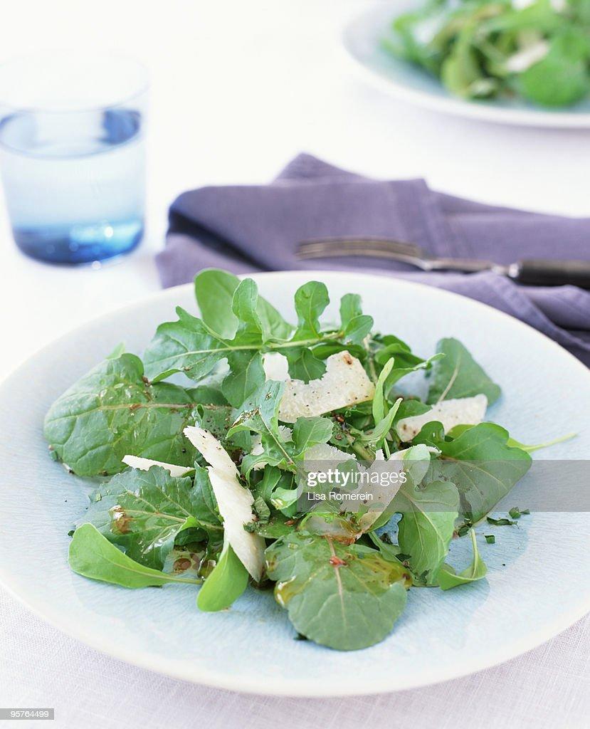 Table setting with arugula parmesan salad